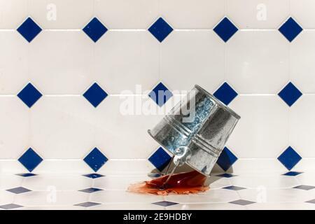 Un secchio di metallo cade sul pavimento e spruzzi fuori il liquido colorato.
