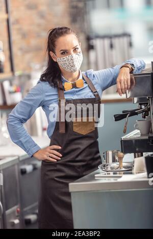 La cameriera alla moda indossa una maschera protettiva mentre prepara un espresso in una caffetteria.