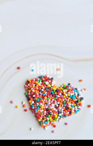 Concetto creativo di amore per le vacanze. Forma a cuore realizzata con piccole caramelle colorate su uno sfondo di marmo bianco. Concetto di San Valentino. Gravidanza concetto di diabete. Vista dall'alto, disposizione piatta. Foto di alta qualità