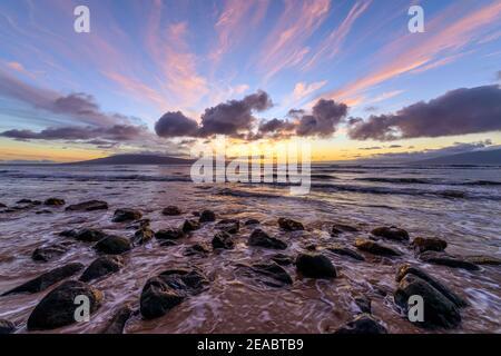 Sunset Rocky Coast - una colorata vista del tramonto su una costa rocciosa della costa nord-occidentale dell'isola di Maui, con l'isola di Lanai all'orizzonte. Maui, Hawaii, Stati Uniti.