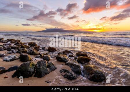 Tramonto tropicale - UN colorato tramonto su una spiaggia rocciosa della costa nord-occidentale dell'isola di Maui, con l'isola di Lanai all'orizzonte. Hawaii, Stati Uniti.