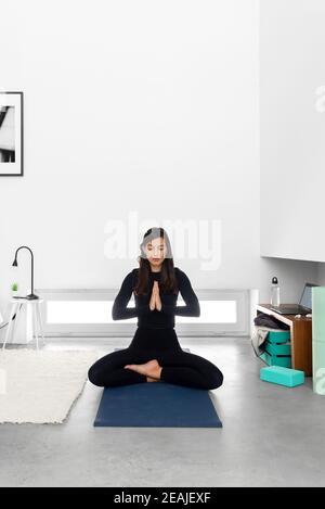 Giovane donna in abbigliamento sportivo seduto in loto posa con namaste mani e meditazione durante la pratica di yoga a casa
