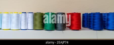 fili colorati per la macchina da cucire sul ripiano, striscione