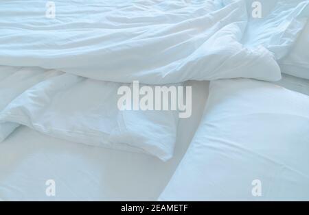 Letto bianco comfort e morbido cuscino nella camera da letto moderna. Coperta di biancheria bianca nella camera da letto dell'hotel. Dettaglio closeup della caucciosa coperta bianca dopo il risveglio al mattino. Comodo letto con soffice piumone bianco. Foto Stock