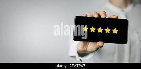 servizio eccellente e feedback dei clienti. donna che tiene il telefono con 5 stelle sullo schermo. spazio per la copia Foto Stock