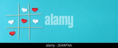 Giocare tic tac TOE con un cuore bianco e un cuore rosso su uno sfondo blu. Concetto per il giorno dell'amore, San Valentino, 14 febbraio. Carta San Valentino. Foto Stock