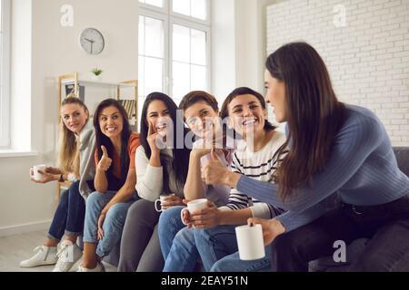 Donne felici che si siedono sul divano, bevono caffè, condividono buone notizie e si sostengono a vicenda