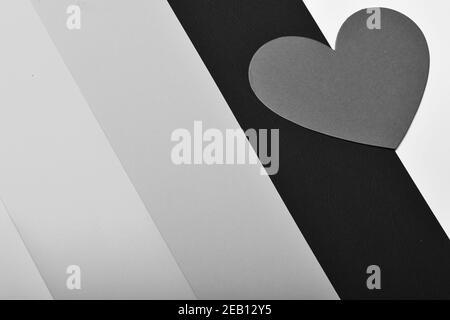 Simbolo di amore e strisce colorate. Carta giornaliera di San Valentino. Cuore di carta rosso su sfondo colorato, vista dall'alto. Concetto di amore e vacanza. Foto Stock