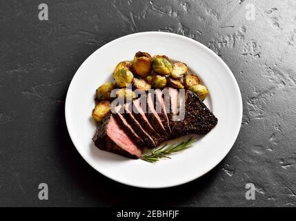 Bistecca di manzo alla griglia con germogli di bruxelles su un piatto su sfondo di pietra nera. Foto Stock