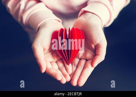 Closeup delle mani del bambino capretto che tengono carta rossa piegata cuore sfondo scuro. Festa di San Valentino. Concetto di supporto, cura e amore. Simbolo del cuore rosso di