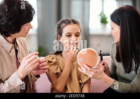 Carino bambina in abito applicando balsamo nutriente sulle labbra mentre guardando nello specchio tenuto dalla giovane donna di brunette che dà il suo consiglio di bellezza