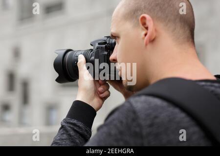 fotografia e concetto di hobby - primo piano vista posteriore di fotografo maschile che scatta foto con la moderna fotocamera dslr Foto Stock