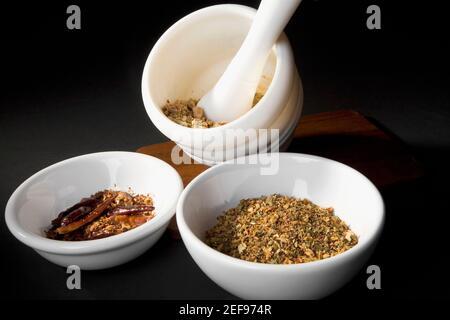 Primo piano di peperoncino in polvere e polvere curcuma in ciotole con mortaio e pestello