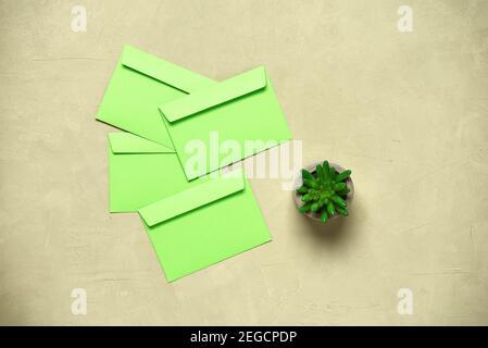 Stazioneria ancora vita. Buste verdi e piante succulente decorative su fondo di cemento beige. Area di lavoro o scrivania da ufficio. Vista dall'alto, disposizione piatta