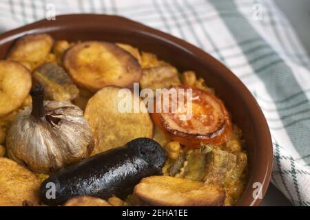 Immagine di una casseruola di argilla in cui tipico riso mediterraneo cotto è stato cotto con budino nero, pomodori, patate, ceci ...