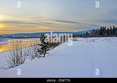 Vista su una riva del fiume innevata e montagne boscose al crepuscolo. Foto Stock