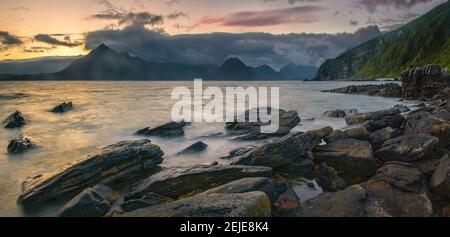 Costa rocciosa di Loch Scavaig con le montagne di Cuillin al tramonto, Isola di Skye, Scozia Foto Stock