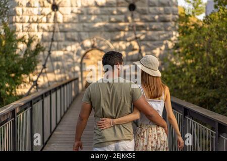 Vista posteriore della giovane coppia, a piedi abbracciata sulla piattaforma di legno del ponte sospeso del fiume Aare nel tardo pomeriggio di settembre al tramonto. Foto Stock