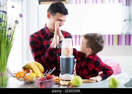Padre e figlio nella stessa camicia sono molto forti mentre aspettano che il frullatore sia fatto in modo che possano avere il loro frullato in una cucina luminosa.