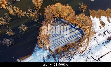 Vista aerea dal drone del piccolo lago a forma di cuore con alberi vicino al grande lago in inverno Foto Stock