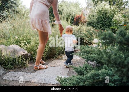 bambino imparando a camminare con l'aiuto di sua madre all'aperto