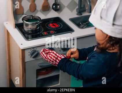 Bambina caucasica, indossando un cappello da chef, giocando ad essere una cuoca nella sua piccola cucina giocattolo. Foto Stock