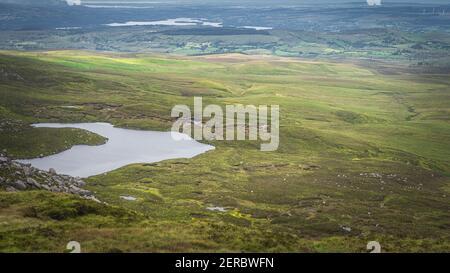 Vista dal Monte Cuilcagh su laghi, prati verdi e campi con macchie di sole nella valle sottostante, Irlanda del Nord
