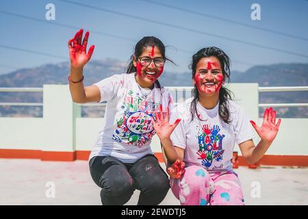 Le giovani donne indù asiatiche che celebrano il festival Holi con l'applicazione di colori l'una all'altra faccia durante il festival. Divertimento con le famiglie. Divertimento per tutta la famiglia