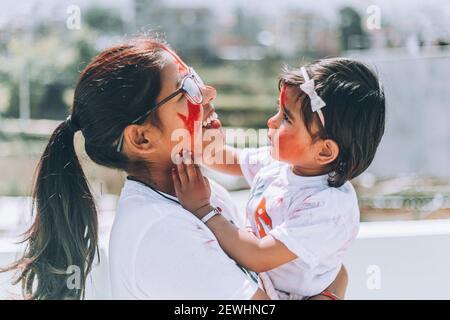 Buona Madre godendo del tempo con il suo bambino durante il festival holi a casa. Divertimento con i bambini. Bambino che si diverta con la famiglia madre.asiatica