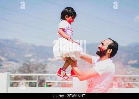 Padre e figlia si divertono durante il festival Holi Purnima o Holi dopo aver applicato i colori l'uno all'altro. Festa dei colori celebrazione. Divertimento per tutta la famiglia, f