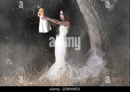Orrore scena di una donna posseduta tenendo una bambola. Foto di alta qualità.