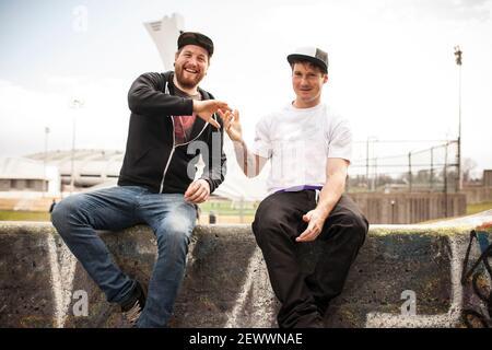Due amici che si bmxing e dando eachother una stretta di mano Foto Stock