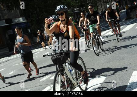 Una donna prende un selfie mentre lei corre in bicicletta lungo Park Avenue vicino 39th Street come l'Avenue è chiuso come parte del programma di New York City 2015 Summer Streets a New York, NY, l'8 agosto 2015. Si tiene tre sabati consecutivi ad agosto dalle 7:00 alle 13:00. Si estende dal ponte di Brooklyn a Central Park, chiudendo Park Avenue al traffico per le persone a correre, a piedi e in bicicletta. (Foto di Anthony Behar) *** utilizzare credito dal campo di credito ***
