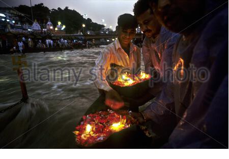 Persone che offrono un profondo (fiori galleggianti e lampada ad olio) al fiume Gange. Haridwar. Uttarakhand. India. Haridwar, Uttaranchal, India. Haridwar è famosa per il suo Ganga Arati, culto di Ganga Maiya, tenuto ogni sera a Har-ki-pari Ghat. Ogni notte (tranne per un breve periodo durante l'estate quando il ghat è pulito e riparato) migliaia di devoti e pellegrini si riuniscono circa un'ora prima del tramonto. (Foto di Sergi Reboredo) *** si prega di utilizzare credito dal campo di credito *** Foto Stock