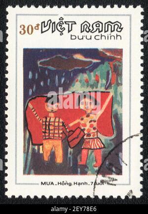 Francobollo. Ragazzo e ragazza sotto la pioggia, dalla serie immagine dipinta da un bambino, Vietnam, circa 1984 Foto Stock