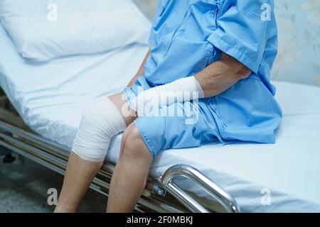 Anziano asiatico anziano o anziano donna anziana paziente incidente al braccio e ginocchio con bendaggio a letto nel reparto di ospedale di cura.
