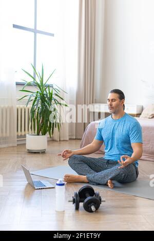 Foto verticale. Pratica di meditazione - l'uomo di mezza età durante la cottura a vapore dello yoga online. Un uomo si siede su un tappetino yoga di fronte a un monitor portatile e medita