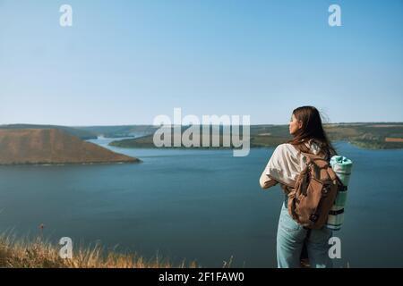 Felice giovane donna con zaino in piedi su alta collina e guardando ampio fiume Dniester. Bella signora che cammina all'aria fresca al parco nazionale Podillya Tovtry