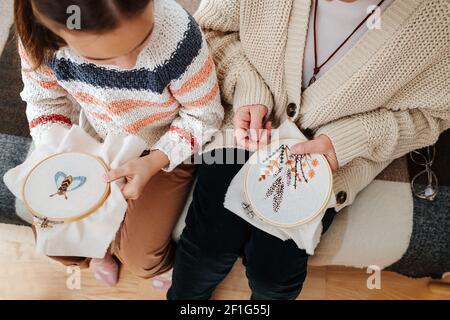 Primo piano delle mani del bambino e della donna anziana, mantengono il loro ricamo in cerchi.