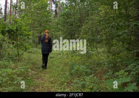 Una ragazza decapitata in una giacca nera e leggings è camminando lungo un sentiero sull'erba verde in un foresta di compensazione tra alberi alti con foglie succose