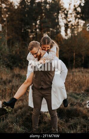 Lo sposo che sposa piggyback ride Foto Stock