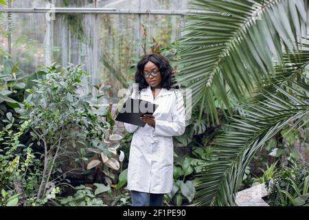 Biologa scienziata femminile professionista, donna africana piuttosto fiduciosa in camice bianco, in piedi in serra facendo note durante il controllo delle piante