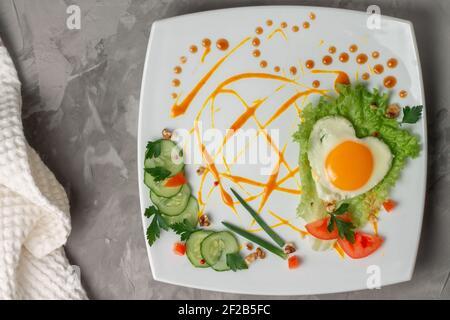 Uovo fritto a forma di cuore con verdure, erbe e salsa su piastra quadrata bianca su fondo grigio in cemento, piatto.