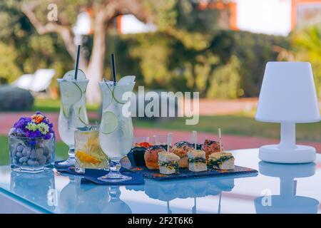 Aperitivo rinfrescante, cocktail e mini snack fatti a mano (sfondo sfocato)