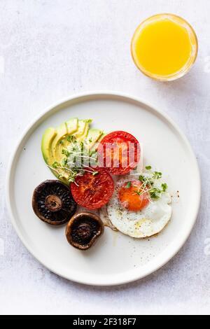 Colazione vegetariana con uova fritte, pomodori, funghi e avocado