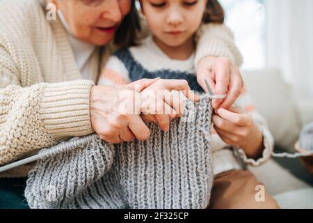 Entusiasta nonna seduta su un divano con sua nipote sta insegnando a lavorare a maglia, tenendo le mani sopra le sue. Primo piano, concentrarsi sulle mani. Facce