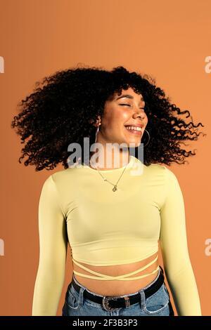 Stock foto di bella donna africana che muove i suoi capelli ricci in studio shot.
