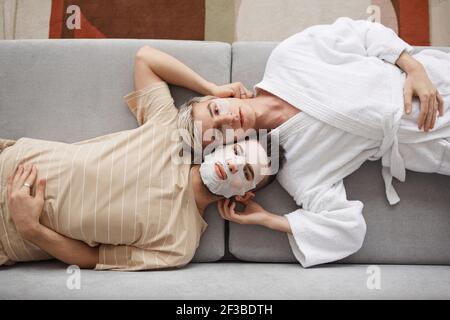 Ritratto dall'alto di una giovane coppia gay che guarda la fotocamera mentre si sdraiava sul divano e indossa maschere facciali, bellezza e concetto di skincare