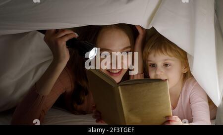 Giovane madre che legge la favola di Goodnight storia alla figlia minore sotto coperta con piumone in camera notte