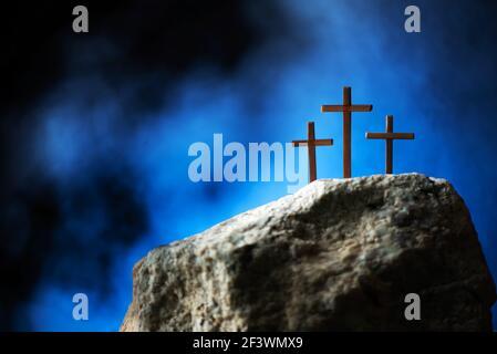 Silhouette di tre croci sulla collina del Calvario, sfondo blu. Crocifissione, risurrezione di Gesù Cristo. Festa cristiana di Pasqua, Golgota. È risorto